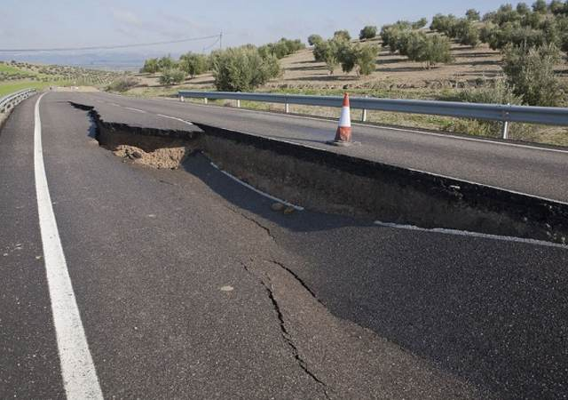 A two-lane road with a giant hole, caused by a landslide, in the middle of the road.