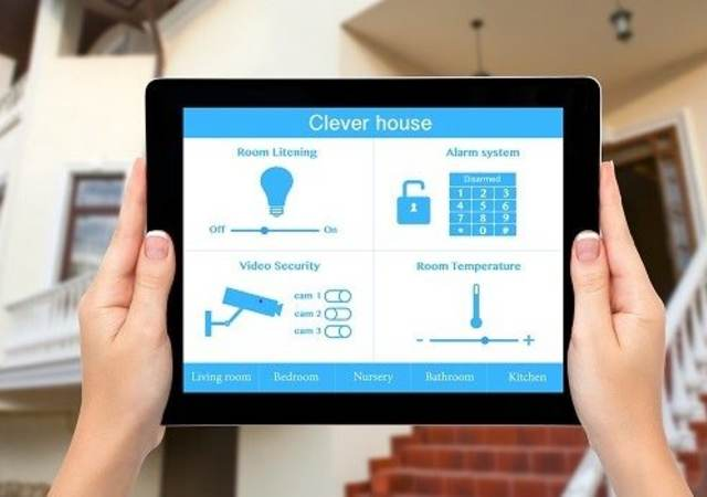 Female hands hold a tablet computer with system clever house on a screen on the background of the house