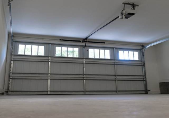 a closed, garage door with automatic opener centered to image.