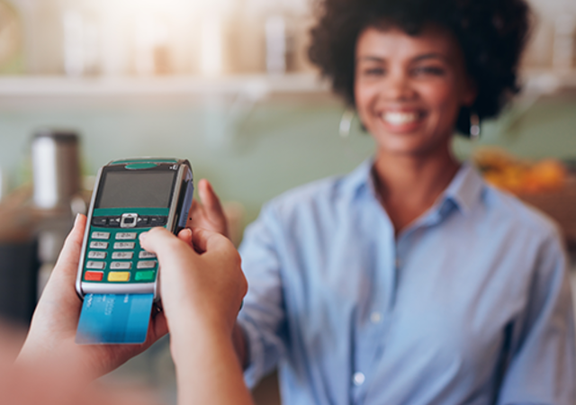 Woman paying for a retail transaction with EMV technology.