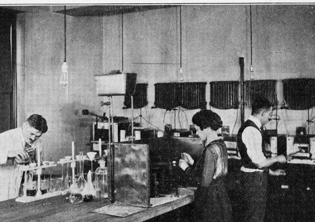 UL chemists workiing on a counter circa 1920s, Group of chemists standing around a long table, conducting experiments, December 1920, , , , , , , , , , ,