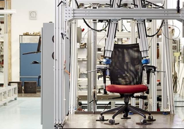 Black office chair with red seat cushion undergoes durability test at Holland, Michigan lab