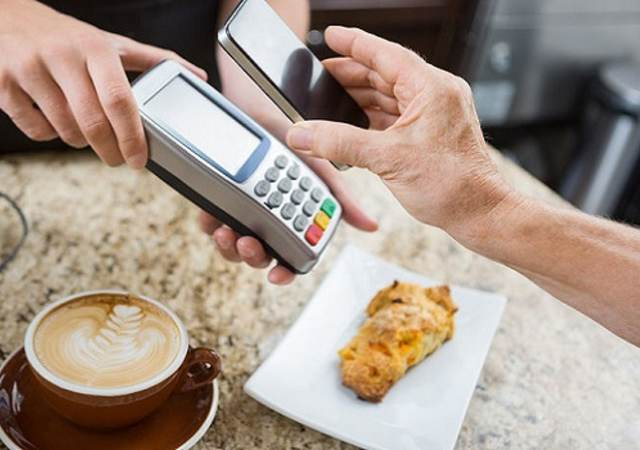 cropped image of customer paying through mobile phone over electronic reader at cafe counter