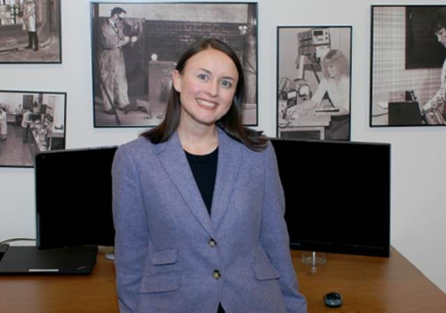 Justine Wagner relaxes in front of photo wall showing UL's history.