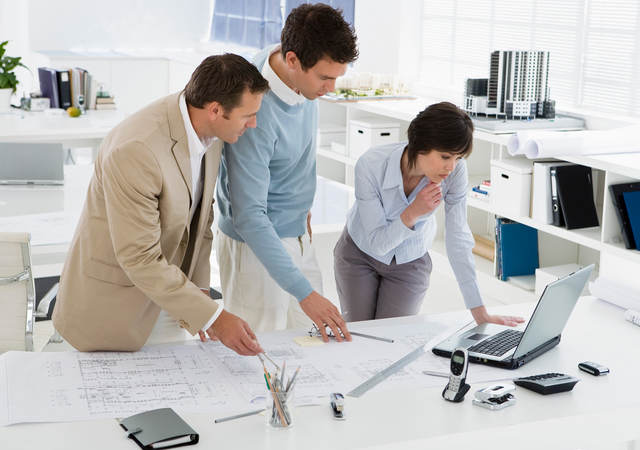 Three businesspeople in an office look at a laptop and blueprints