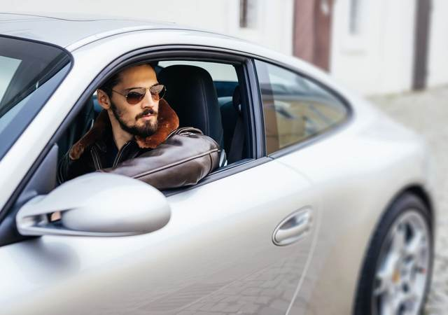 Handsome man sitting in a silver Porche