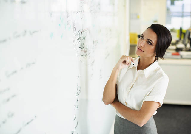 Woman studying information on a whiteboard