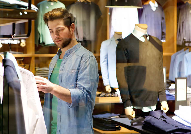A man browses different articles of clothing.