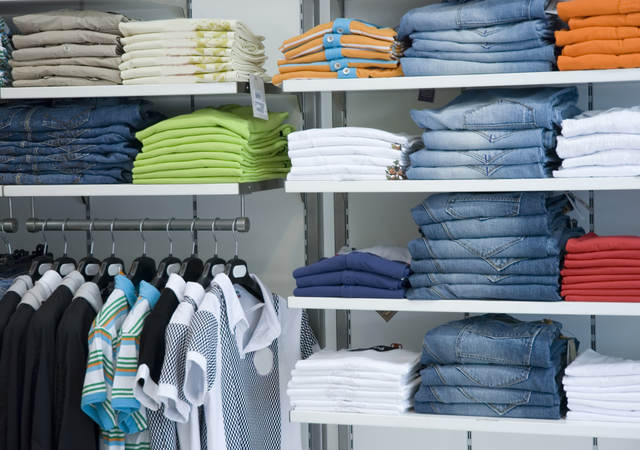 Retail store shelves filled with neatly folded clothes arranged by color.