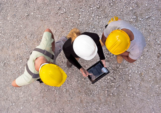 Workers on-site collaborating on a tablet