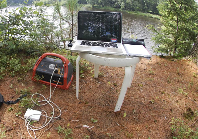 Portable power pack connected to laptop in a nature scene.