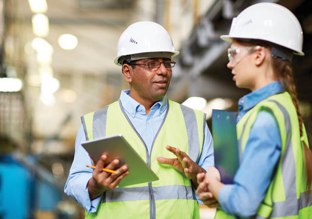 male and female factory workers talking on factory floor with tablet wearing hard hats and safety vests