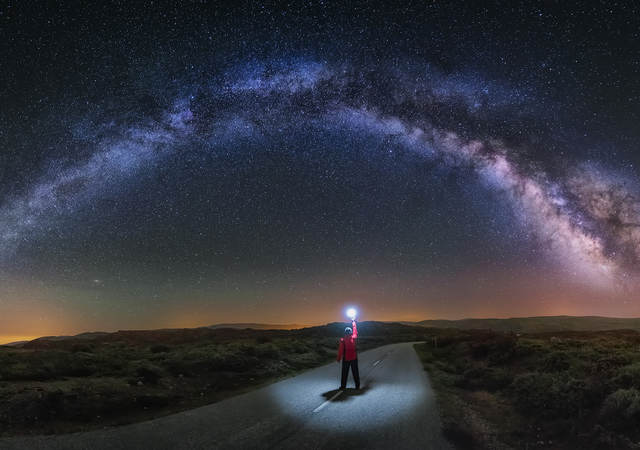 A young man on a road watching the Milky Way and lighting the road with a flash.