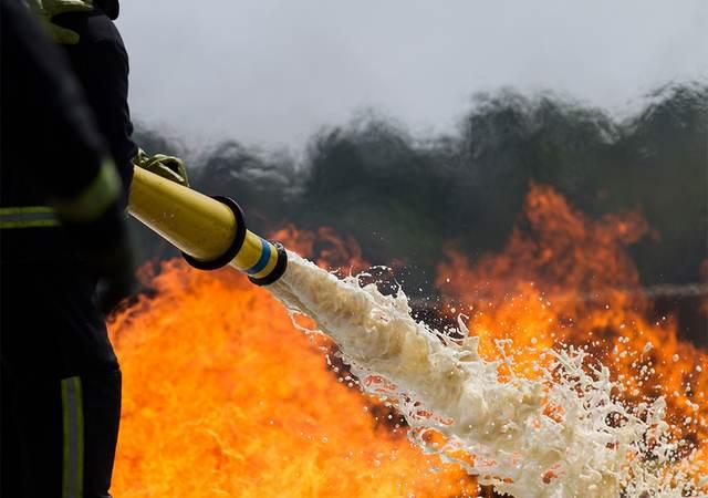 Firefighter spraying a fire with foam hose