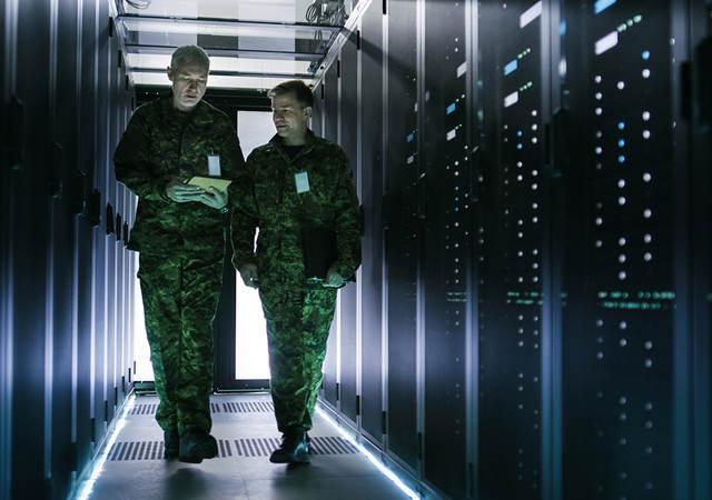 Two military men walking in data center corridor