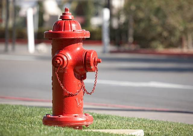 A bright red fire hydrant along a road.