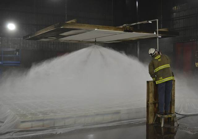 UL engineer in safety gear testing a water mist firefighting system in a laboratory