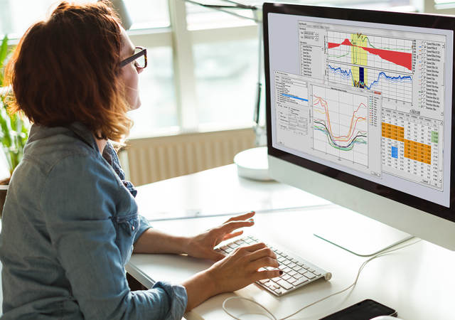 Wind energy analyst sitting at computer working on Windographer software.