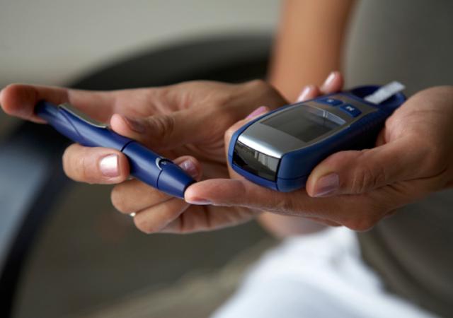 Woman taking blood sugar level w/glucometer