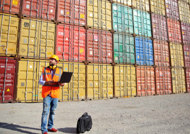 Man in orange vest/yellow hard hat in yard of shipping containers
