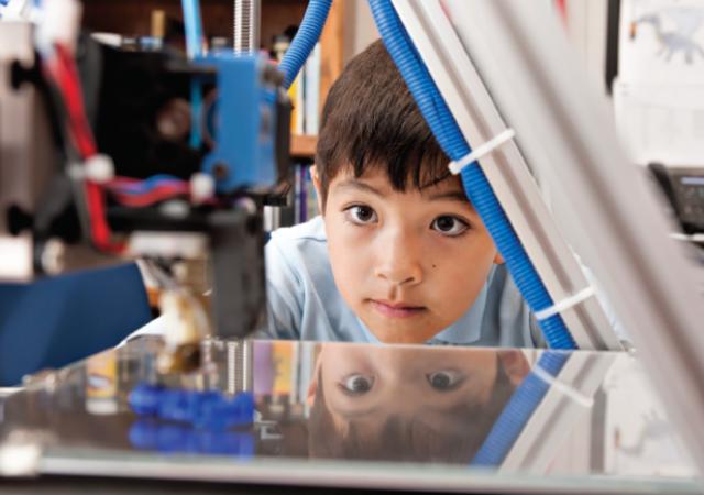 Young boy looking at a 3D printer