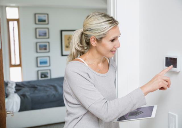 Woman holding tablet while touching keypad screen on wall