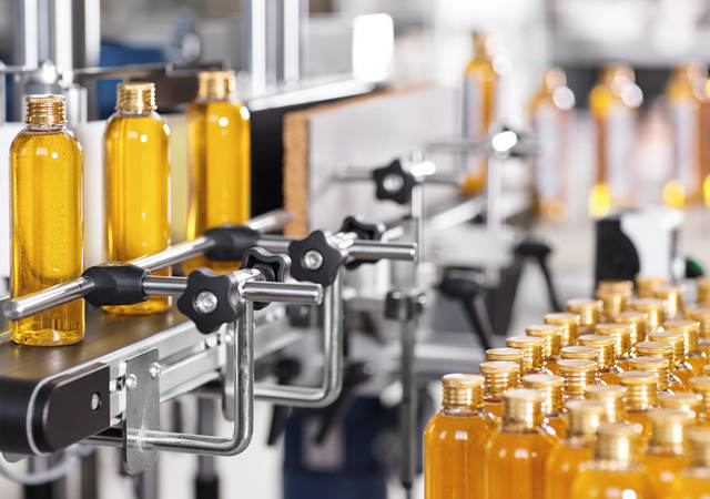 Bottles filled with liquid moving through the manufacturing process.