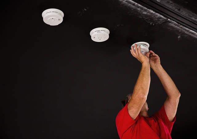 UL engineer installing smoke detectors for testing