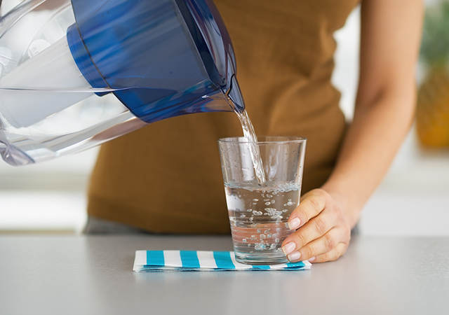 woman pouring a glass of water from a filter jug