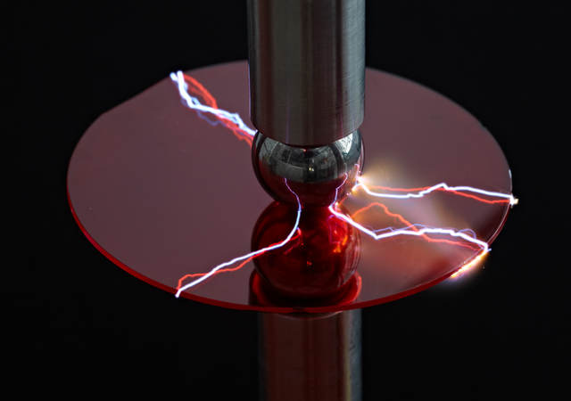 A machine using electricity to test a piece of plastic.