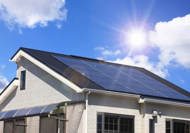 The sun shines brightly on the solar panels installed on the roof of a white, stucco home.