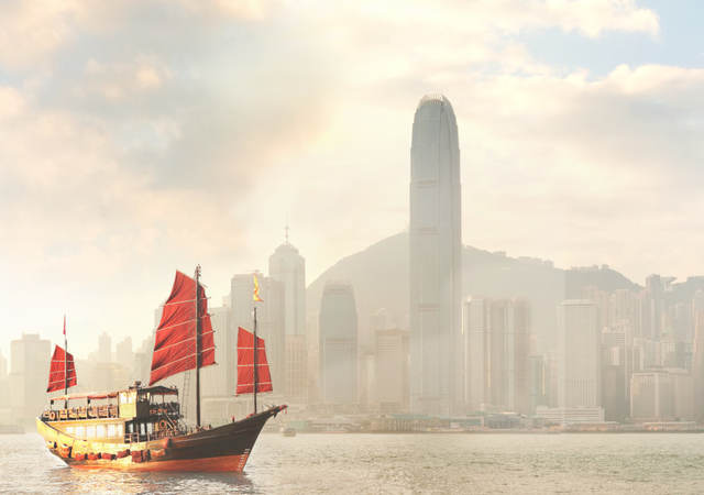 A boat sailing in front of a large city.
