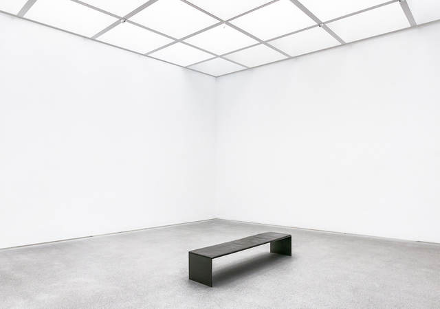 A black bench in the middle of a white room.