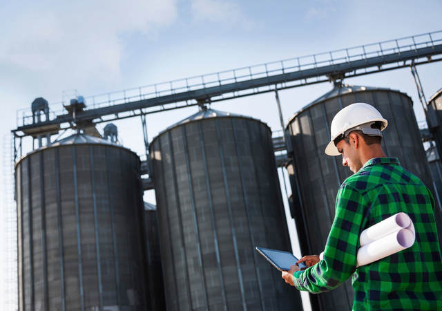 Person working on iPad outside of large silos