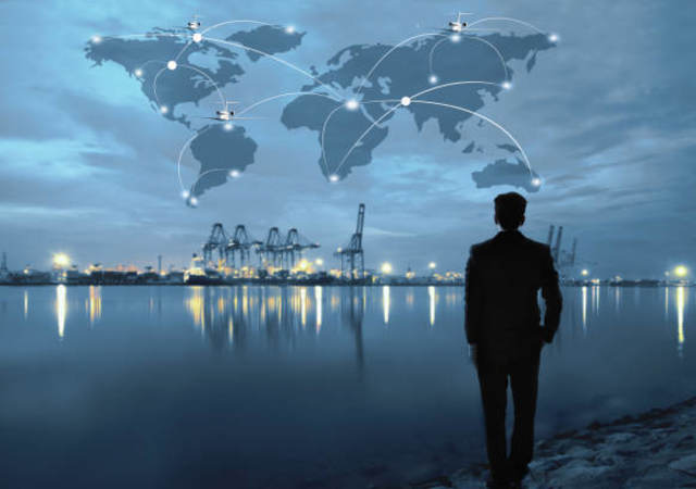 Man at a lake with night skyline and superimposed world map