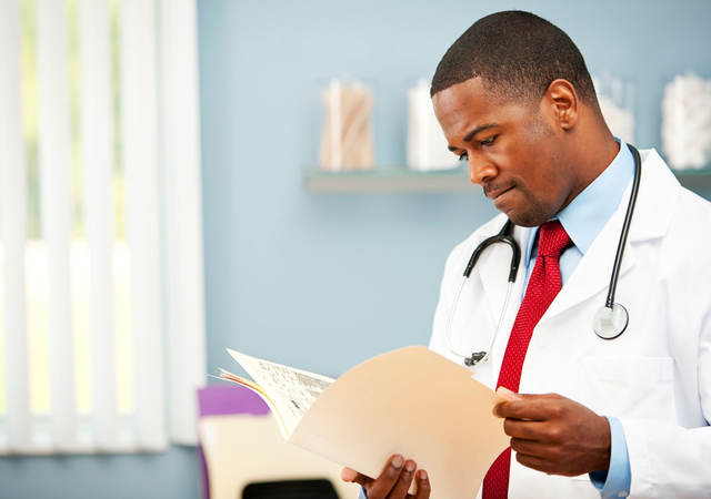 African American Doctor looking at patient file