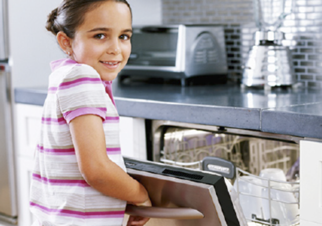 school age girl in a home kitchen opening dishwasher