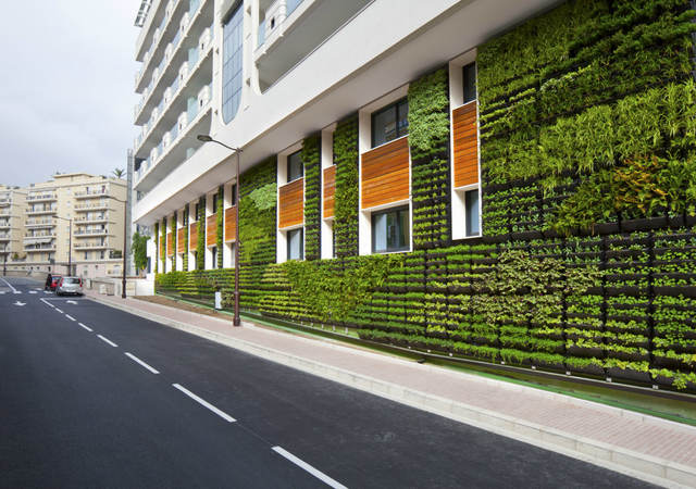 Sustainable urban building with exterior garden walls, large windows, and wood paneling