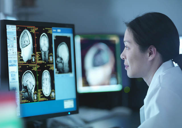 Woman in front of screen with medical scans