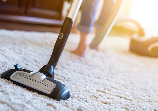 Woman using vacuum cleaner while cleaning carpet in house