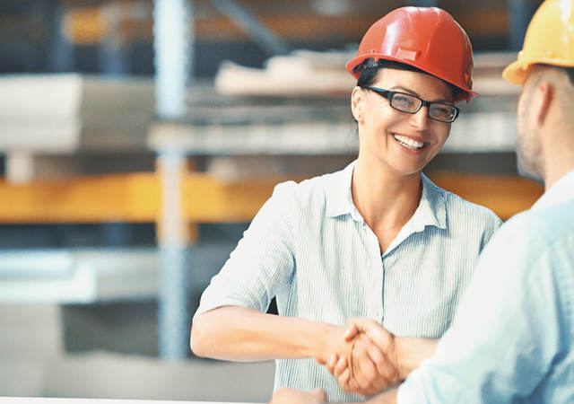 Two people in hardhats shaking hands.