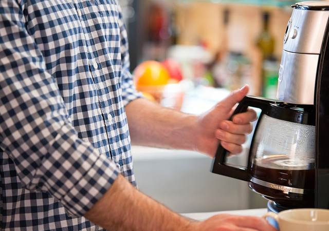 Consumer using a coffee maker