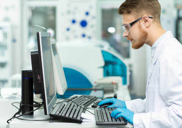 Two scientists in lab coats looking at a tablet screen.