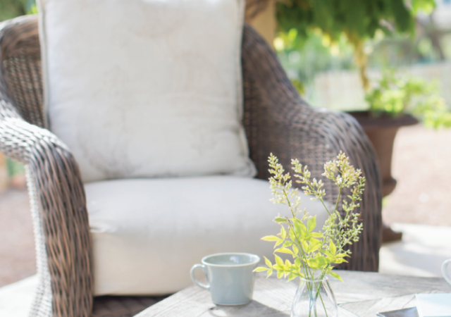 Wicker chair with cushions by coffee table outdoors