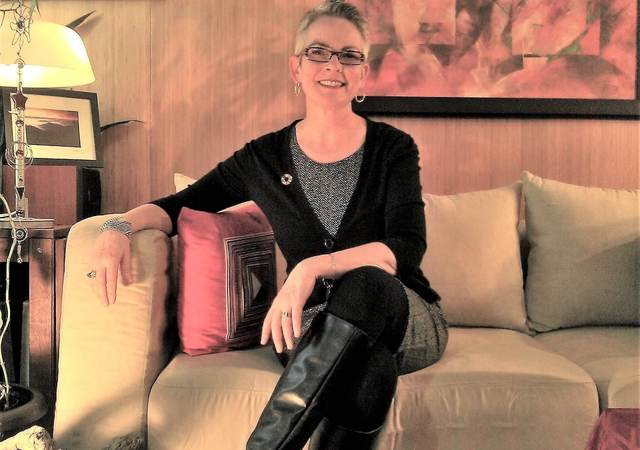 Catherine Sheehy, head of Advisory Solutions, poses in a black sweater, grey shirt, black pants and black boots.