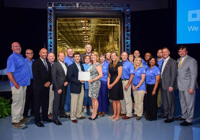 The BASF Zero Waste team stands in front of a mock-up of their facility as they accept their Zero Waste certification.