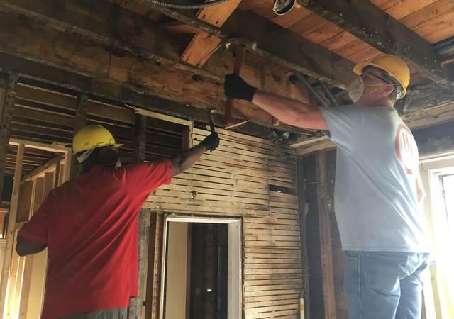 UL volunteers tear down wood furring in historic Elgin, Illinois home.