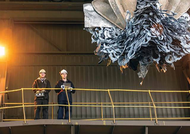 2 men overlooking a claw picking up recycleables
