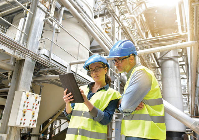 Man and women in hard hat and safety glasses in industrial facility looking a tablet
