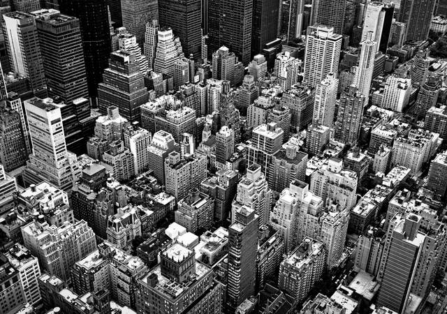 A black and white photo of the densely packed New York City landscape.